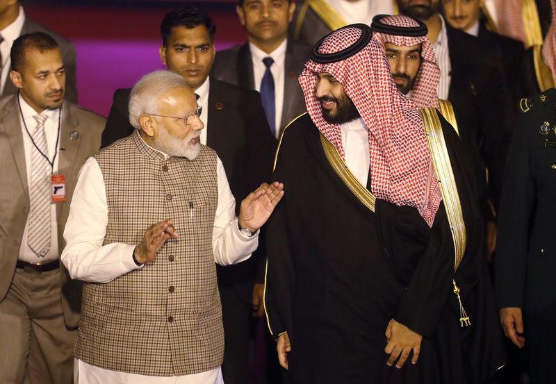 India's Prime Minister Narendra Modi talks to Saudi Arabia's Crown Prince Mohammed bin Salman upon his arrival at an airport in New Delhi
